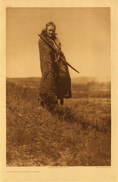 Edward S. Curtis - Plate 198 A Grizzly Bear Brave- Piegan border=